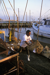 Stock photo of a man standing on shore unloading bags from a ship