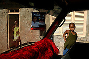 A woman and a small boy on a street in Vila do Maio (Maio Village). Inside the van a political banner from Carlos Veiga,  the presidential candidate who lose the election for the second time.