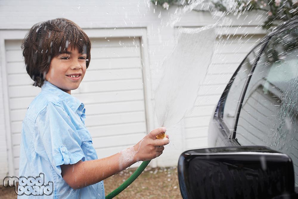 Boy (7-9) washing car with hose