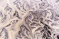 Amazing abstract formations. Black sand and white glacial river stream.