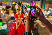23 NOVEMBER 2013 - BANGKOK, THAILAND: A fan takes a picture of a perfomer of the Prathom Bunteung Silp mor lam troupe backstage during a performance in Bangkok. Mor Lam is a traditional Lao form of song in Laos and Isan (northeast Thailand). It is sometimes compared to American country music, song usually revolve around unrequited love, mor lam and the complexities of rural life. Mor Lam shows are an important part of festivals and fairs in rural Thailand. Mor lam has become very popular in Isan migrant communities in Bangkok. Once performed by bands and singers, live performances are now spectacles, involving several singers, a dance troupe and comedians. The dancers (or hang khreuang) in particular often wear fancy costumes, and singers go through several costume changes in the course of a performance. Prathom Bunteung Silp is one of the best known Mor Lam troupes in Thailand with more than 250 performers and a total crew of almost 300 people. The troupe has been performing for more 55 years. It forms every August and performs through June then breaks for the rainy season.              PHOTO BY JACK KURTZ