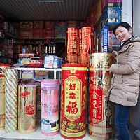 Hunan, Liuyang, Dec. 19..2013 : we DONT HAVE THE NAME OF THIS WOMAN WHO ALSO WORKS IN THE RETAIL PLACE.  She s posing next to giant firecrackers for the Chinese market.