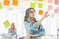 Creative businesswoman reading sticky notes on glass wall with colleague working in background at office