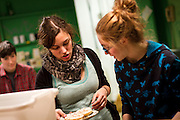 Erica Hauswald '12, left, brings out a custom-made, cream cheese and cayenne pepper bagel to Sophie Haas '12 in Bob's Underground Café on Thursday night.
