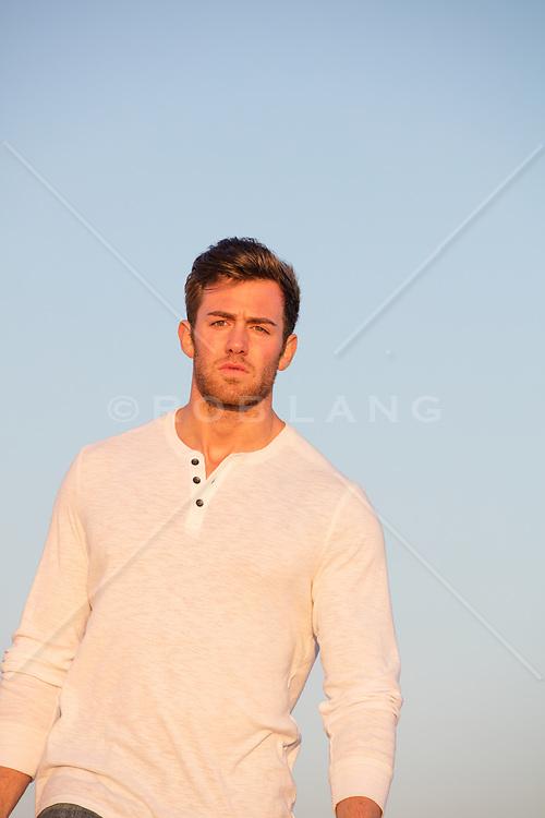 good looking man walking at sunset