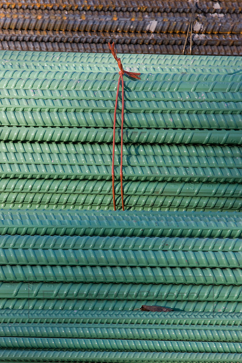 Green and rusted re-bar sit stacked on a road construction site