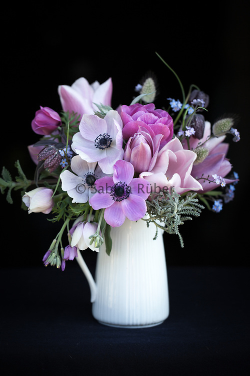 Soft pink and purple Flower arrangement with Anemones, Tulips and Fritillaria meleagris in white china jug