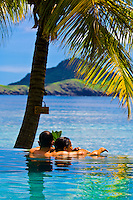 Couple enjoying view from infinity pool, Tokoriki Island Resort, Fiji Islands
