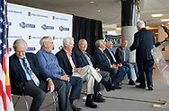 Garden City, New York, U.S. June 6, 2019. After speaking at lectern on stage, at extreme right, ANDY PARTON, President of Cradle of Aviation Museum, turns to guests sitting behind him, L-R, Apollo 16 Lunar Pilot CHARLIE DUKE, Apollo Flight Director MILT WINDLER, Apollo 9 Lunar Pilot RUSTY SCHWEICKART, Apollo 13 Lunar Pilot FRED HAISE, Apollo 17 Lunar Pilot HARRISON SCHMITT, Apollo Flight Director GERRY GRIFFIN, and Apollo 7 Lunar Pilot WALT CUNNINGHAM, during Cradle of Aviation Museum's Apollo Astronauts Press Conference during its day of events celebrating 50th Anniversary of Apollo 11.