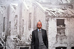 © Licensed to London News Pictures. 04/04/2012. London, UK.  Harry Allpress (93) the oldest of the Allpress family leans against a wall featuring an image of houses damaged in the Blitz.  Photo call and preview for the Imperial War Museums new A Family in Wartime exhibition. The exhibition features the life on the Home Front during the Second World War, explored through the eyes of one London based family, the Allpress. Photo credit : Stephen SImpson/LNP