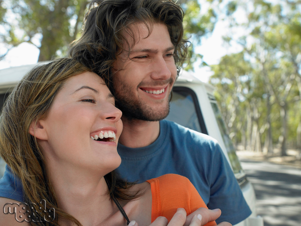Young couple embracing leaning against front of van parked by road head and shoulders