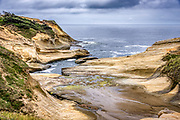 Cove and cave on the northside of the Cape Kiwanda peninsula in Pacific City, Oregon.