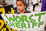"""19 JUNE 2009 -- PHOENIX, AZ: A boy carries a sign in opposition to Maricopa County Sheriff Joe Arpaio during the demonstration against the sheriff Friday at the Wells Fargo Bank building. The Sheriff's Department is headquartered in the Wells Fargo Bank building. Rev. Al Sharpton was in Phoenix Friday to protest the high profile """"crime suppression"""" sweeps conducted by the Sheriff's Department. Critics contend the sweeps use racial profiling to target Hispanics. PHOTO BY JACK KURTZ"""