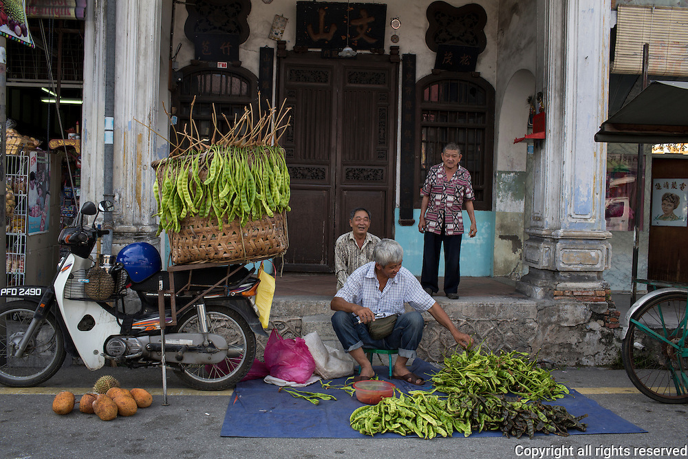 men sell petai, a strong smelling bean that is foraged from the enarby jungle. The bean is cooked into savory items. Balik Pulau, Penang, Malaysia