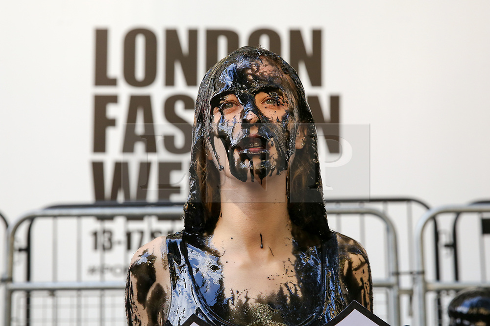 """© Licensed to London News Pictures. 13/09/2019. London, UK. A campaigner from People for the Ethical Treatment of Animals (PETA) protests against the hazardous waste associated with the leather industry is covered in black """"toxic slime"""" on the opening day of London Fashion Week. Photo credit: Dinendra Haria/LNP"""