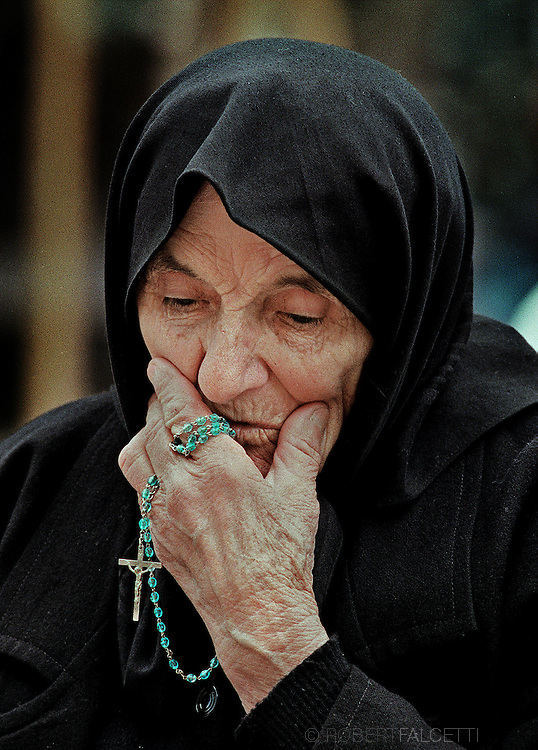 MEDJUGORJE, BOSNIA-HERCEGOVINA:  Polish pilgrim Anna Rabek kisses her Rosary while sitting outside St. James Parish Church in Medjugorje. The small parish of about 4,000 has become famous due to a series of reported visions of the Virgin Mary. The visions that began in 1981 and still continue today, attract thousands of pilgrims each year. The apparitions have not been validated by the Catholic Church.   (Photo by Robert Falcetti). .