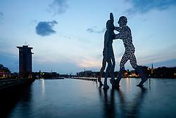 Dusk view of Molecule Man sculpture on Spree River in Berlin, Germany