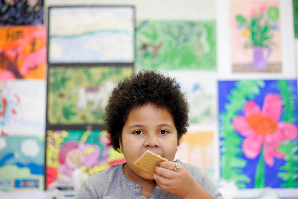 Michael Zamora/Caller-Times.Sariah Boston, 7, licks the extra frosting off of the wall of the graham cracker house she is building Thursday, Dec. 22, 2009 during an art class at the Vacation Station day camp at Galavan Elementary in Corpus Christi.