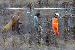 Offchurch, UK. 24th August, 2020. A HS2 worker monitors anti-HS2 activists during tree felling works alongside the Fosse Way in connection with the HS2 high-speed rail link. The controversial HS2 infrastructure project is currently expected to cost £106bn and will destroy or significantly impact many irreplaceable natural habitats, including 108 ancient woodlands.