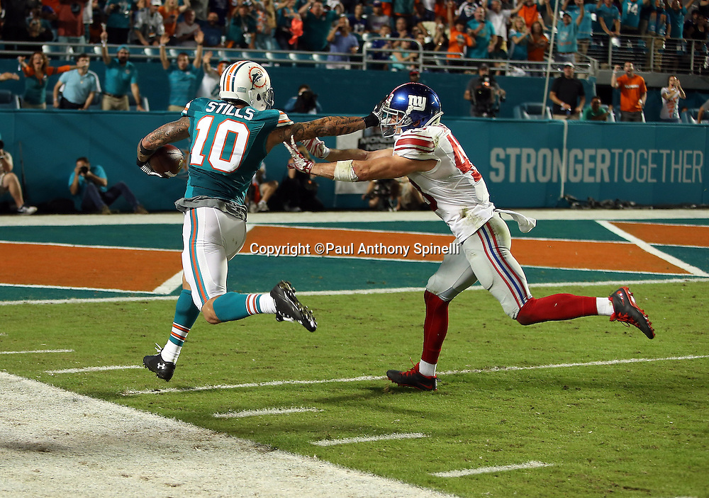 Miami Dolphins wide receiver Kenny Stills (10) straight arms New York Giants defensive back Craig Dahl (43) as he catches a 47 yard third quarter touchdown pass good for a 24-17 Dolphins lead during the NFL week 14 regular season football game against the New York Giants on Monday, Dec. 14, 2015 in Miami Gardens, Fla. The Giants won the game 31-24. (©Paul Anthony Spinelli)