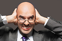 Bald businessman holding hand over ears looking sideways making a face