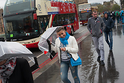 Tourist cover herself with an umbrella amid rain and wind, at Westminster Bridge, London, UK, 14th May, 2013. Photo by: Daniel Leal-Olivas / i-Images