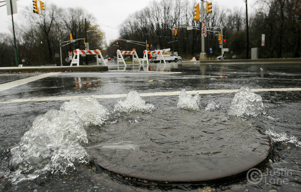 Water rushes out of a manhole on a closed street in New Milford, New Jersey on Monday 16 April 2007. A large storm delivered records amount of rain to the East Coast of the United States over the weekend and today, causing New Jersey to declare a state of emergency.