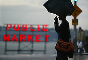 An umbrella and pedestrian on First Avenue  are silloueted against a darkening sky early in mid afternoon.  (Steve Ringman / The Seattle Times)