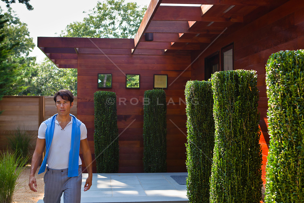 well dressed Asian American man outside a beautiful home in The Hamptons