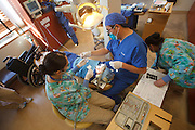 Kenji Saisho, M.D., D.D.S., treats a patient Tuesday, Dec. 13, 2011, at Central Coast Pediatric Dental Group in Salinas, California. With him are Emelda Ramirez, R.D.A., left, and Maria Placensia, R.D.A.