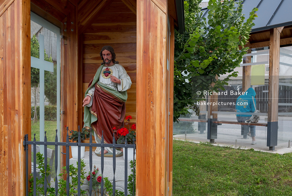 A Christian religious shrine with a Jesus figure with a person waiting for a bus at a bus stop in rural Slovenia, on 18th June 2018, in Bohinjska Bela, Bled, Slovenia.