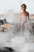 A girl stands next to a pile of smoking charcoal at a wood charcoal production site on the outskirts of San Pedro, Bas-Sassandra region, Côte d'Ivoire on Sunday March 4, 2012. Men, women and children - who don't go to school - work here seven days a week.
