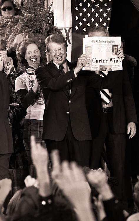 "Carter cousin Betty Pope reacts as President-elect Jimmy Carter holds a newspaper with the headline ""Carter Wins"" as he celebrates with crowds filling the streets of tiny Plains, Georgia, on election night."