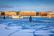 Fartyg går förbi Skeppsholmen en isig vinter i Stockholm