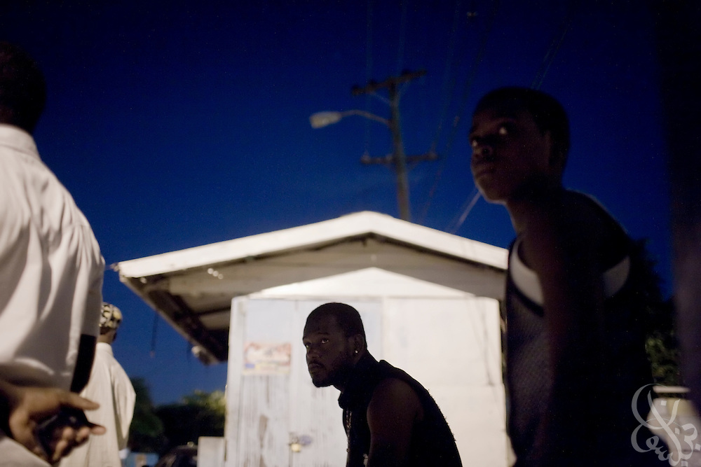 """Rema """"Action Pak"""" garrison gang members stand watch as lookouts on a corner of their public housing scheme December 13, 2008 in the Rema Garrison/Trenchtown area of central Kingston. Because of the strength of ghetto gangs, often law enforcement is ill-equipped to enter or enforce rule of law in the garrisons of inner city Kingston. In the absence of legitimate law enforcement then, gangs fulfill a self-proclaimed community protector/enforcer role and function as defacto police, judge and juries on their turf."""