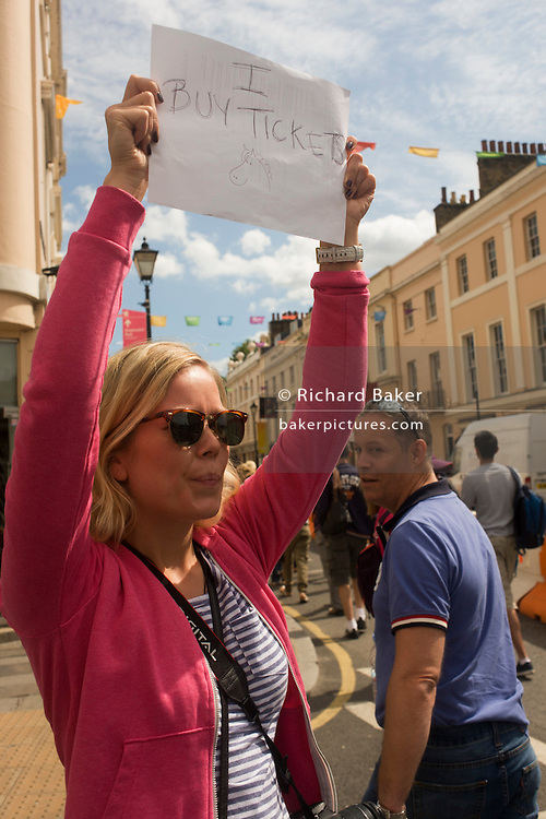 London 2012 Olympic spectator holds a home-made sign asking for unwanted equestrian tickets as visitors arrive along the old streets of Greenwich, London. On the day that 3,000 extra tickets were put on sale after criticism of empty seats at some events, sports fans were desperate to see the eventing and dressage on day 4 of the London games.