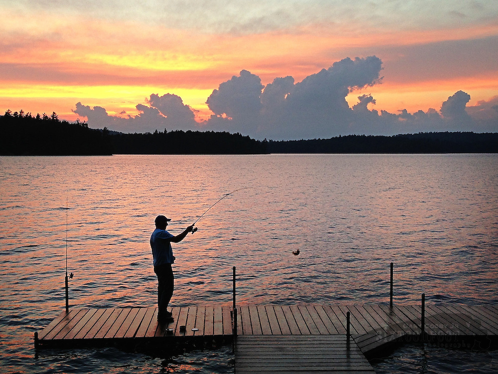 Joe Jackson fishes from a pier on Tupper Lake in Adirondack Park near Tupper Lake, New York as the sun goes down painting the water and the sky with the hues of sunset.  Photo by Gary Cosby Jr.