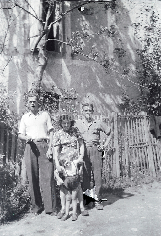 family with friend and young child posing outside the house rural France 1950s