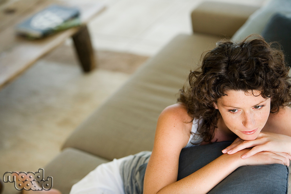 Woman sitting on couch in living room elevated view