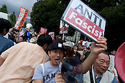 A young man holds an anti fascist sign at a protest against the revision of article 9 of the Japanese Constitution outside the Prime-Minister's house in Kasumigasaki, Tokyo, Japan. Monday June 30th 2014. Over 10,000 people showed their support for Japan's unique peace constitution and called on the government to halt its reinterpretation of Article 9 allowing Collect Self Defence which is expected to become law on July 1st