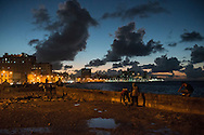 Cubans, some of them fishing, gather on the Malecón at dusk in Havana, Cuba. The Malecón is an esplanade, roadway and seawall that stretches for 8 kilometers along the Atlantic coast in Havana, Cuba.