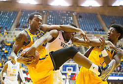 Dec 5, 2015; Morgantown, WV, USA; Kennesaw State Owls guard Kendrick Ray (0) and West Virginia Mountaineers forward Jonathan Holton (1) get tangled for a loose ball during the second half at WVU Coliseum. Mandatory Credit: Ben Queen-USA TODAY Sports