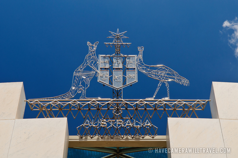 """The Australian Coat of Arms atop Parliament House, Canberra. The emblem features a kangaroo and an emu and a shield. Parliament House is the meeting place of the Parliament of Australia. It is located in Canberra, the capital of Australia. It was opened on 9 May 1988 by Queen Elizabeth II, Queen of Australia.[1] Its construction cost was over $1.1 billion. At the time of its construction it was the most expensive building in the Southern Hemisphere. Prior to 1988, the Parliament of Australia met in the Provisional Parliament House, which is now known as """"Old Parliament House""""."""