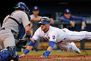 Kansas City Royals' Alex Gordon dives into home plate to score as Los Angeles Dodgers catcher A.J. Ellis is unable to make the tag in the fourth inning of a baseball game at Kauffman Stadium in Kansas City, Mo., Wednesday, June 25, 2014.  (AP Photo/Colin E. Braley)