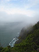 Ocean mist climbs the cliffs along the Pacific coastline.