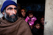 Kabul: 35 year old Zazabour, a mother of 8, her husband Khuman and her youngest son, Sameed at their makeshift home at Tamil Mill Bus site in Kabul city. ..Tajik and Pashtun families live side by side without any major conflict at the Tamil Mill Bus site. Over 70% of the families are returnees from the period 2002-2004 who are unable to achieve sustainable reintegration in their places of origin and subsequently drifted to Kabul City in search of work...There is a nearby school which is accessible to the children but the poor economic circumstances of the many families oblige them to send their children out to work. low levels of literacy, particularly amongst the women, limit their access to employment other than the lowest paid daily wage labor...Afghanistan. /UNHCR/Jason Tanner/February 2011