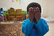 A young African girl at Lambano Sanctuary, a hospice and care home for children with HIV.  She is playing peek-a-boo in the living room.