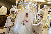 A bride prepares to enter a wedding hall for her Betasher - a ceremony of revealing the bride's face - at a traditional Kazakh wedding in Astana, Kazakhstan.