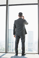 Full length rear view of mature businessman using cell phone white standing near window