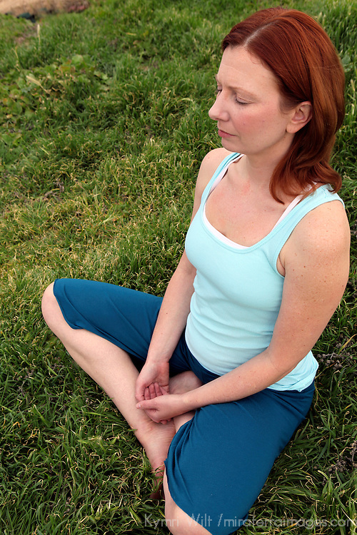 USA, California. Natural woman, healthy, 30's to 40's, doing yoga outdoors.